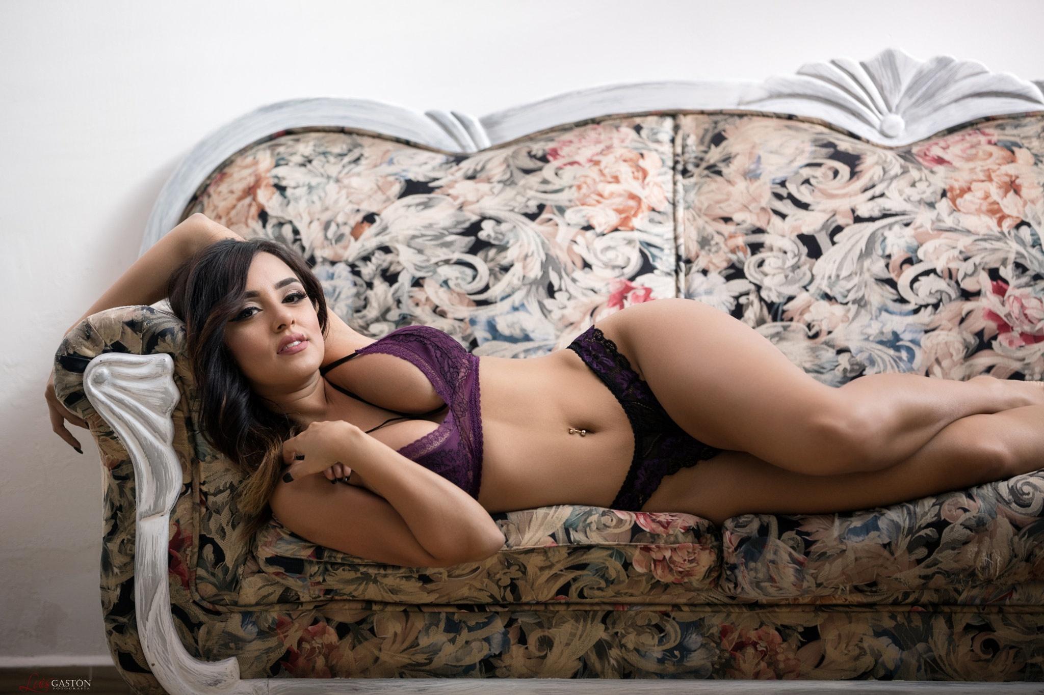 Картинка: Брюнетка, Luis Gaston, модель, лежит, диван, формы, грудь, ножки, взгляд, поза, нижнее бельё, пирсинг
