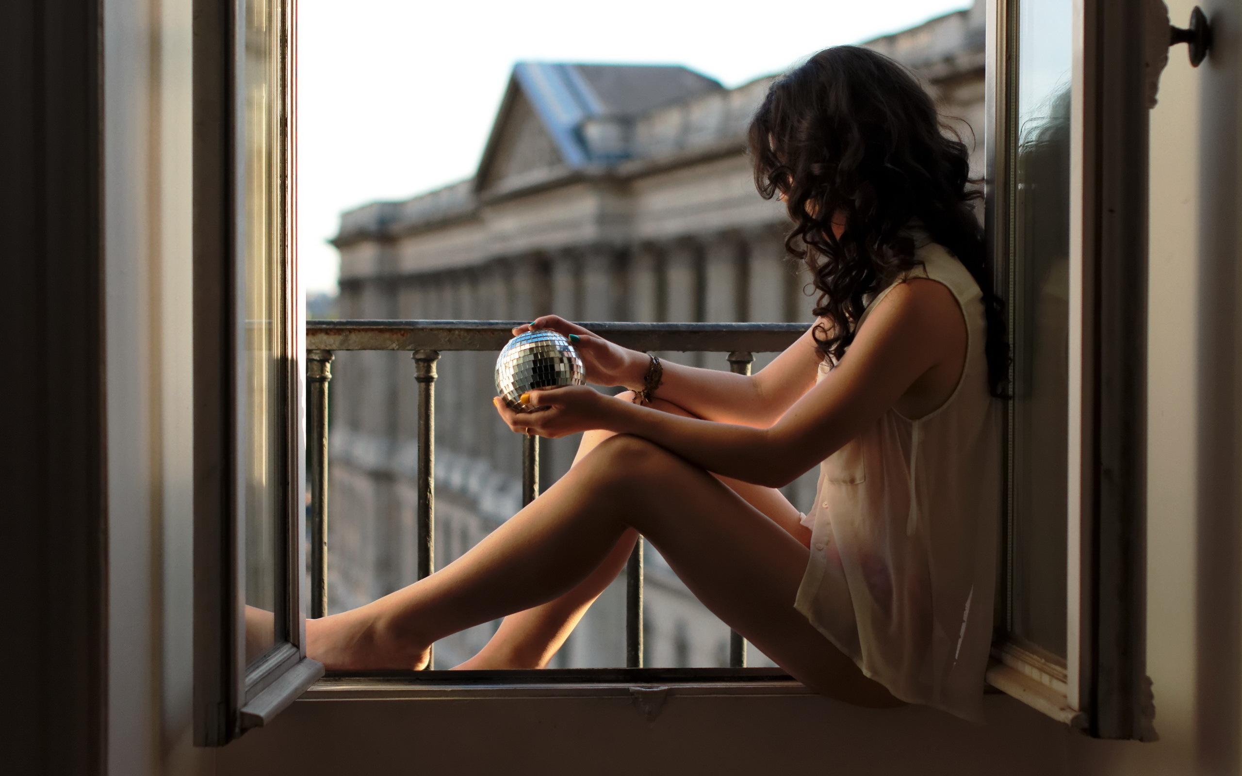 Картинка: Девушка, брюнетка, волосы, кудри, ножки, блузка, сидит, окно, стеклянный шар, ограждение, здание