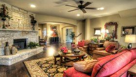Картинка: Гостиная, камин, камень, пол, ковёр, столик, растения, цветы, зеркало, ваза, кресло, диван, подушки, комод, торшер