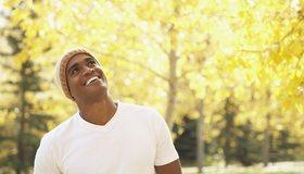 Картинка: Мужчина, улыбается, смотрит, шапка, футболка, парк, боке