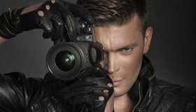 Картинка: Взгляд, улыбка, мужчина, фотоаппарат, объектив, линза, перчатки, куртка, шпион